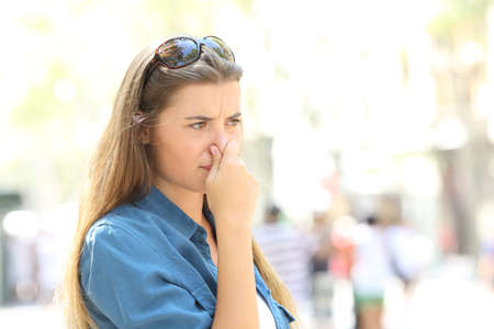 Girl covering her nose due to bad odour in the street Stock Photo