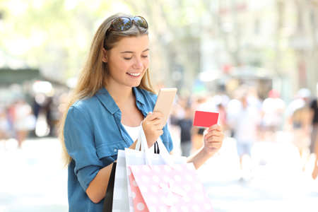 Happy whopper paying online with credit card and a smart phone in the street