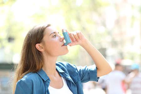 Retrato de vista lateral de una mujer asmática con un inhalador al aire libre en la calle Foto de archivo
