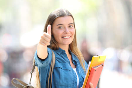Portrait of a happy student in the street with thumb up with a blurred background