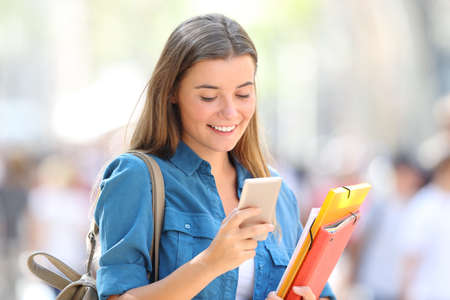 Studente felice utilizza uno smart phone che cammina per strada Archivio Fotografico