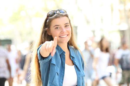 Einzelne glückliche Frau, die zeigt und Kamera betrachtet, die in der Straße steht