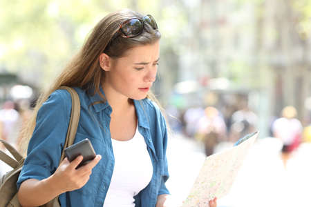 Lost tourist searching direction in a map and a phone in the street