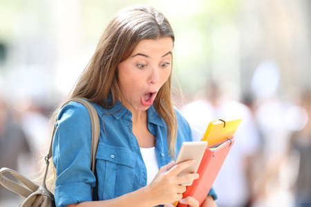 Surprised student receiving good online news in the street Stock Photo