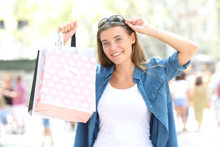 Front view portrait of a happy shopper showing blank shopping bags in the street