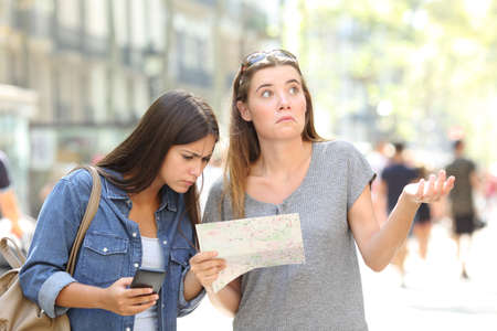 Two lost tourists consulting a paper map and a smart phone searching location in the street