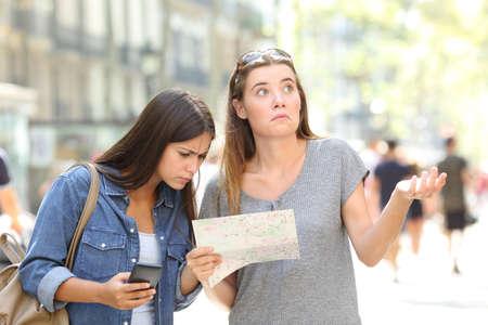 Dos turistas perdidos consultando un mapa de papel y un teléfono inteligente buscando ubicación en la calle Foto de archivo