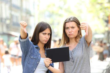 Dos amigos enojados sosteniendo una tableta gesticulando los pulgares hacia abajo en la calle Foto de archivo