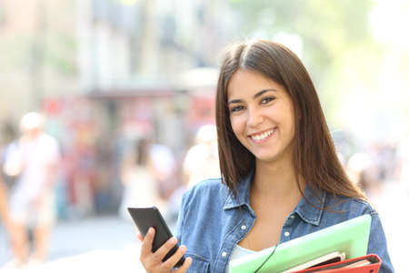 Happy student posing looking at camera holding a smart phone and folders in the street Stock Photo