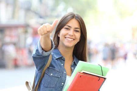 Glücklicher Student, der mit Daumen hoch posiert und Sie auf der Straße ansieht Standard-Bild