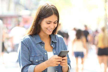 Happy teen uses a smart phone standing in the street Standard-Bild