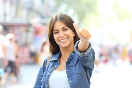Happy girl posing with thumb up looking at camera in the street Stock Photo
