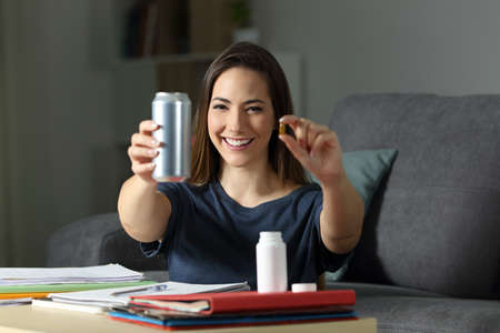 Front view portrait of a happy student showing energy drink and vitamin pill in the night at home Banco de Imagens