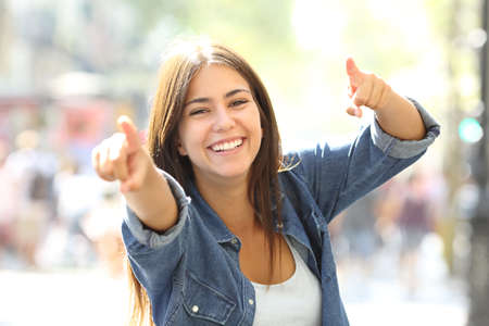 Joyful girl pointing at camera with both hands in the street