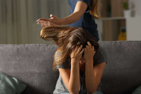 Woman hitting to a sister or roommate sitting on a couch in the living room at home