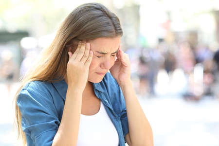 Painful girl suffering migraine touching temple in the street Stock Photo
