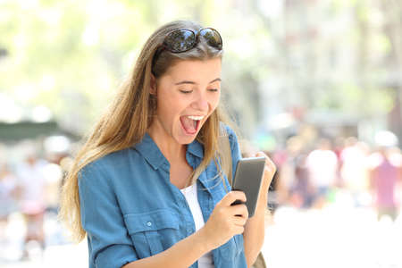 Excited girl reading good news holding a smart phone in the street Stock Photo