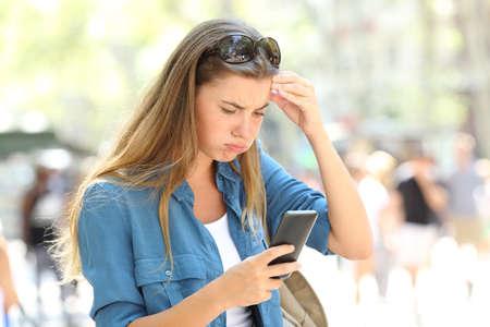 Gefrustreerde vrouw die online slimme telefooninhoud leest in de straat