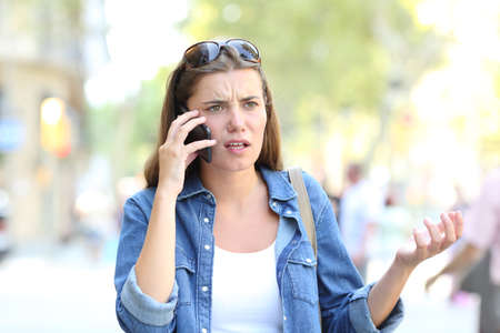 Confused woman having a negative mobile phone conversation in the street