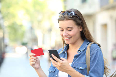 Happy woman paying online with a credit card and a smart phone outdoors in the street