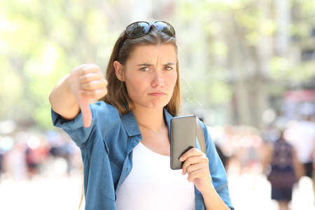 Annoyed woman holding a smart phone looking at camera with thumbs down in the street