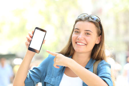 Smiley girl pointing to a blank smart phone screen mock up in the street