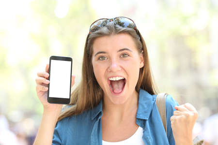 Front view portrait of a excited woman showing a smart phone screen mockup in the street Stock Photo
