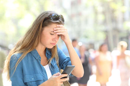 Worried woman reading online smart phone content in the street Stock Photo