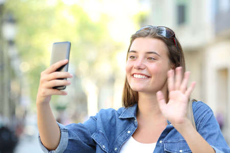 Happy girl waving hand greeting during a phone video call in the street