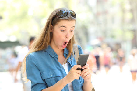 Surprised woman reading online smart phone text in the street