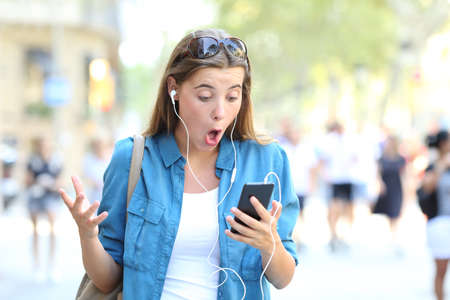 Surprised woman listening to music and watching online content in a smart phone in the street Stock Photo