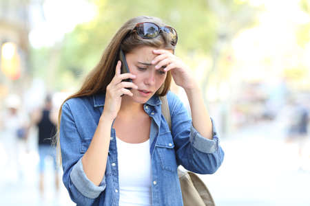 Worried woman having a mobile phone conversation walking in the street Stock Photo