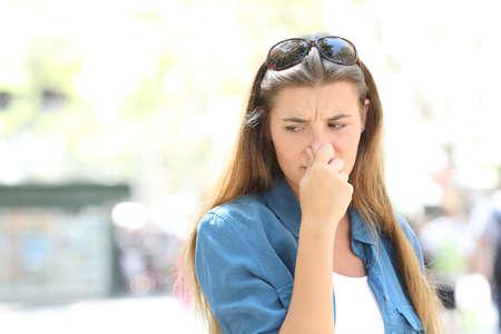 Chica tapándose la nariz en medio de una calle de la ciudad contaminada