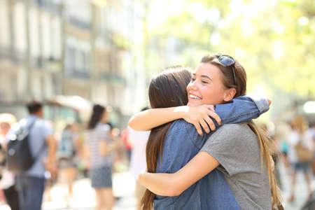 Freunde treffen und umarmen sich auf der Straße Standard-Bild