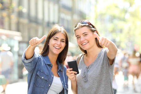 Happy friends holding a smart phone looking at you with thumbs up in the street Stock Photo