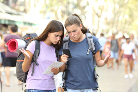 Two lost backpackers confused with gps location using a smart phone in the street
