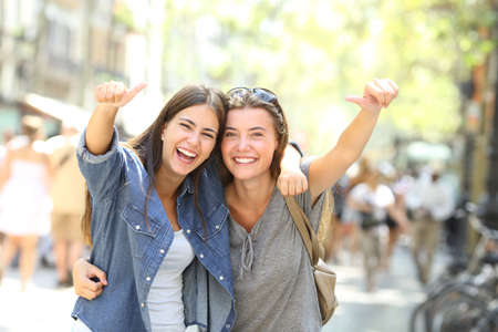 Front view portrait of two cheerful friends laughing loud looking at camera with thumbs up