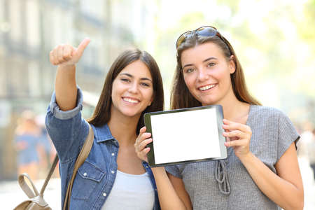 Front view portrait of a positive friends showing a blank tablet screen in a street