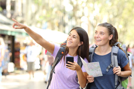 Two happy backpackers sightseeing in a big city street pointing at landmarks