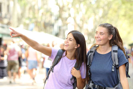 Happy backpacker friends sightseeing and pointing landmarks in the street Stock fotó