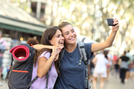 Backpacker friends taking selfie with a smart phone in the street Stock Photo