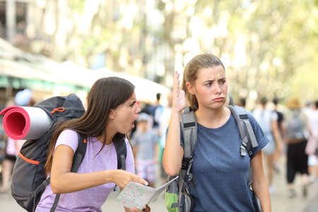 Angry backpackers arguing during vacation travel in a big city street Foto de archivo