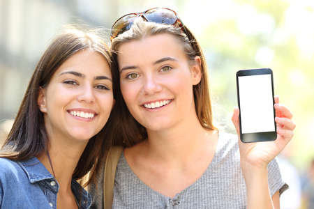 Front view portrait of a friends with perfect smile showing blank phone screen in the street