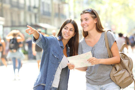 Happy girl helping to a tourist who asks direction in the street Standard-Bild