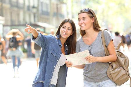 Ragazza felice che aiuta a un turista che chiede direzione in strada Archivio Fotografico - 107735759