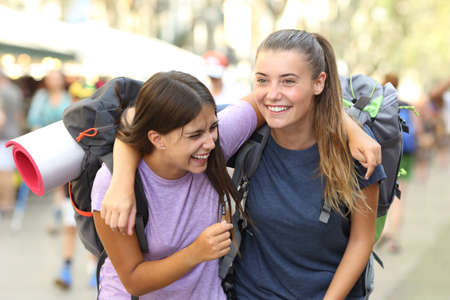 Happy backpackers laughing enjoying vacation in a city street