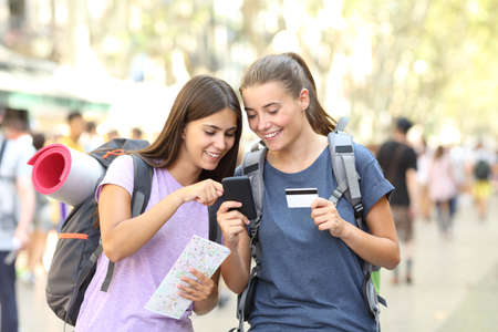 Two happy backpackers searching online content in a smart phone in the street