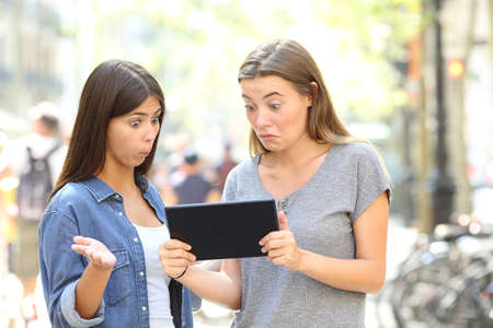 Two confused friends reading online content in a tablet in the street Stock Photo
