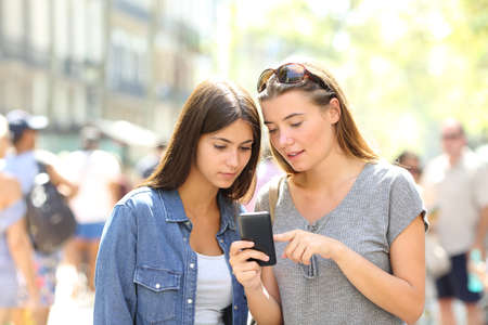 Two girls talking about online content in a smart phone in the street