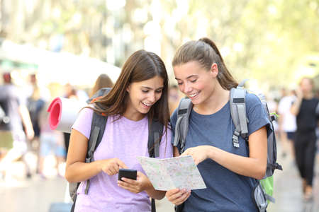 Two happy backpacker friends searching location in a map in the street Stock Photo